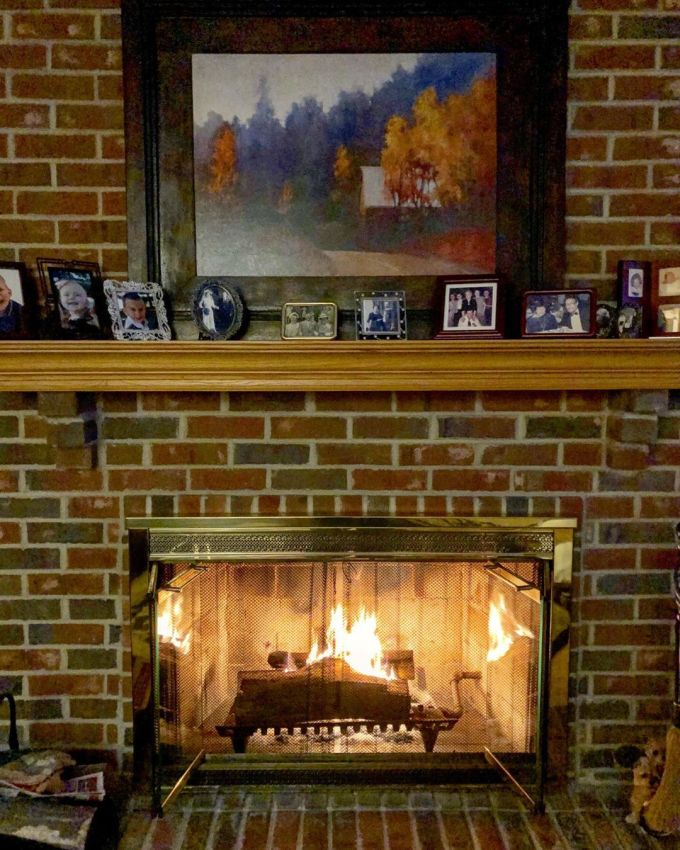Fireplace with a fire going inside it with family photos on the mantlepiece