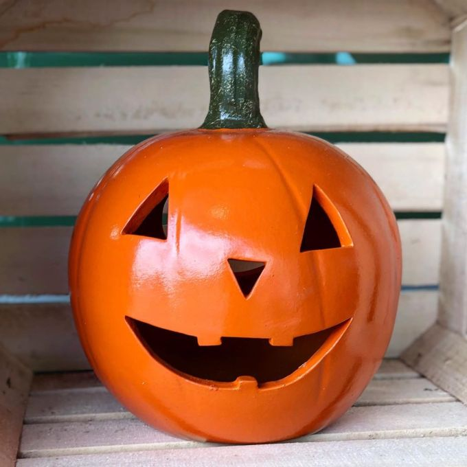 Decorative Halloween jack-o'-lantern on display in a wooden crate