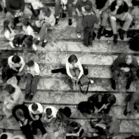 A woman sits by herself with a wide space around her with a wider circle of lots of people around that