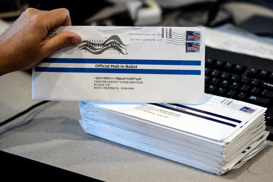 Person holds up an official mail-in ballot for the American General Election for 2020 with a pile of postmarked envelopes on the table beside it