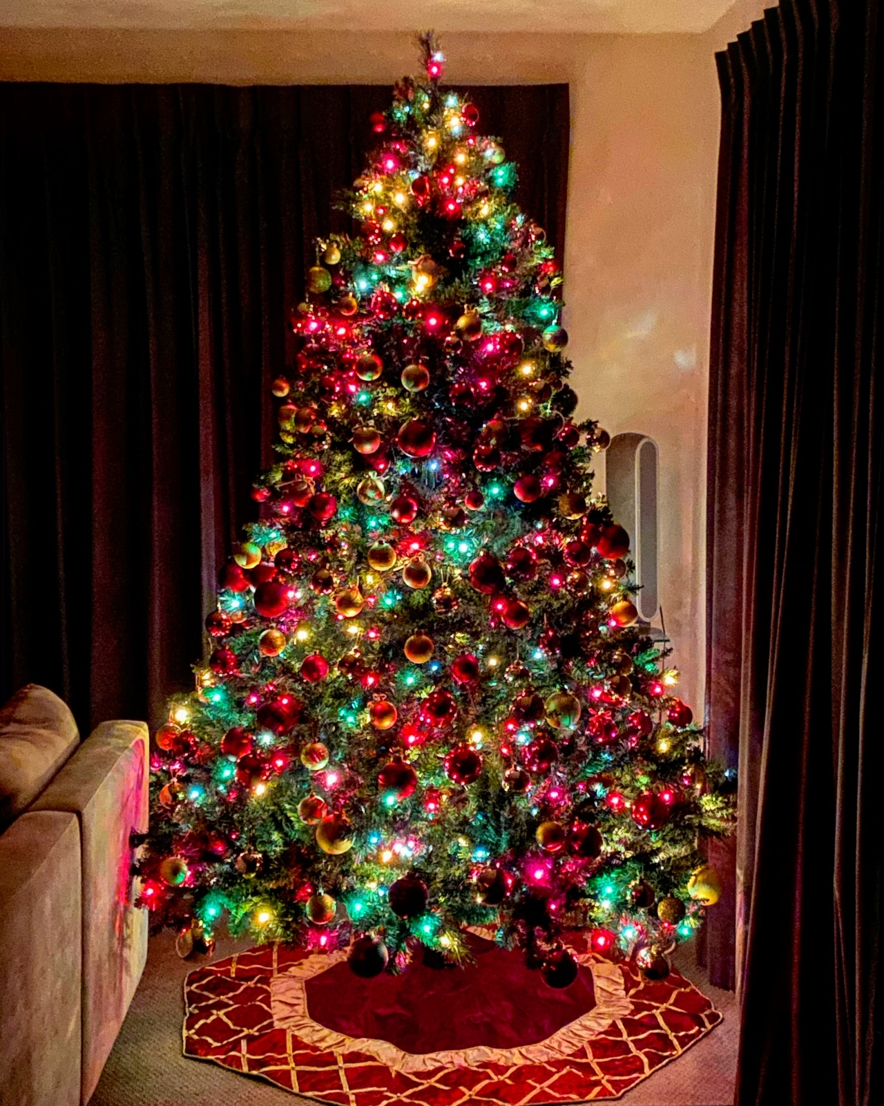 Traditional Christmas tree with gold and red ornaments and red, yellow, green, and blue lights