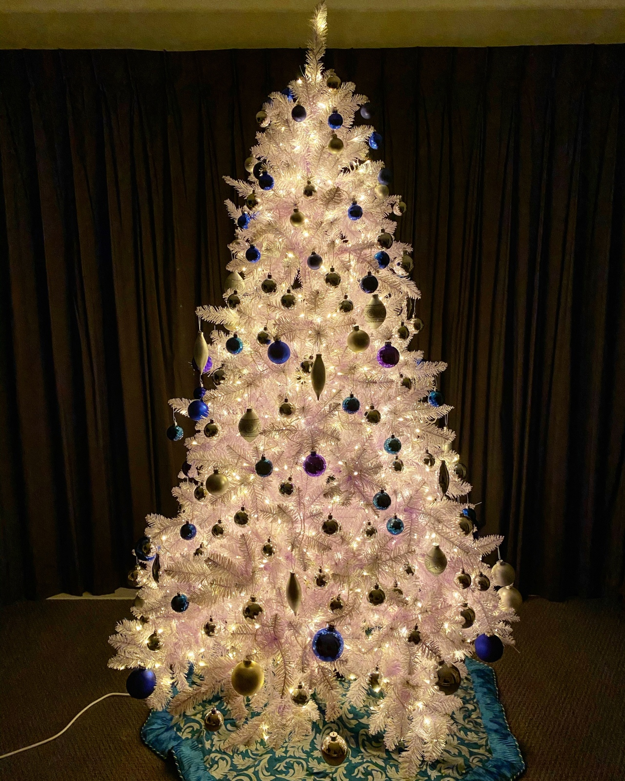White Christmas tree with blue, teal, and silver ornaments, illuminated with warm white LED lights