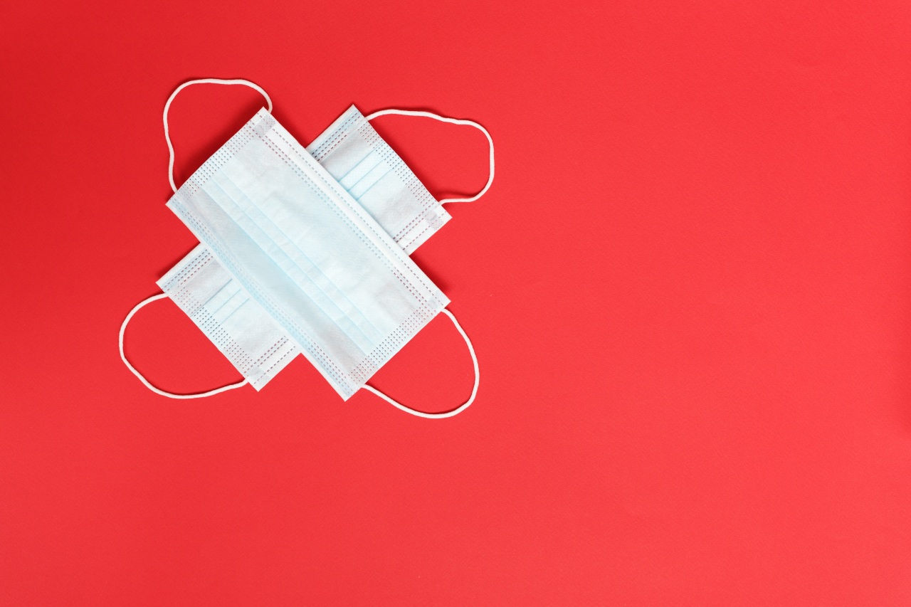 Two surgical masks in the shape of a sideways cross on a red background