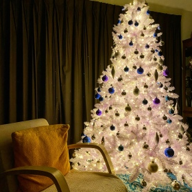 White Christmas tree with white LED lights and blue and silver ornaments, with a reading chair with an orange pillow beside it