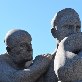 Statue of an anguished man with an older woman trying to comfort him from Vigeland Statue Park in Oslo, Norway