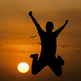 Silhouette of a young man jumping for joy with the sun rising behind him