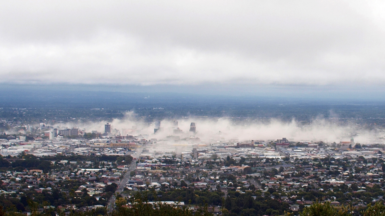 Dust rises from the city of Christchurch moments after the 22 February 2011 earthquake at 12:51 PM