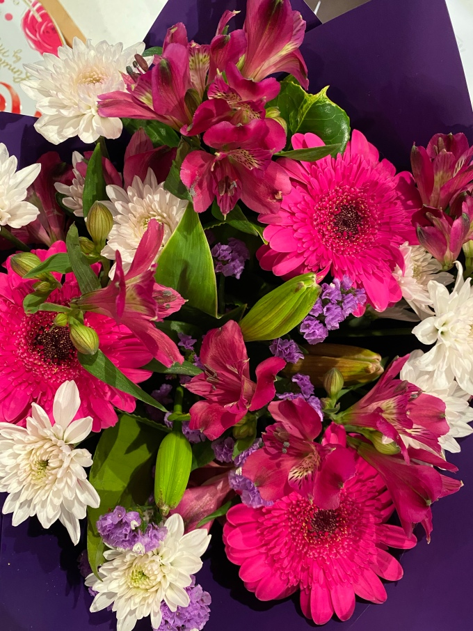 Bouquet of beautiful pink, purple and white flowers surrounded by purple paper