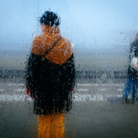 People stand blurred behind a condensation-laden window