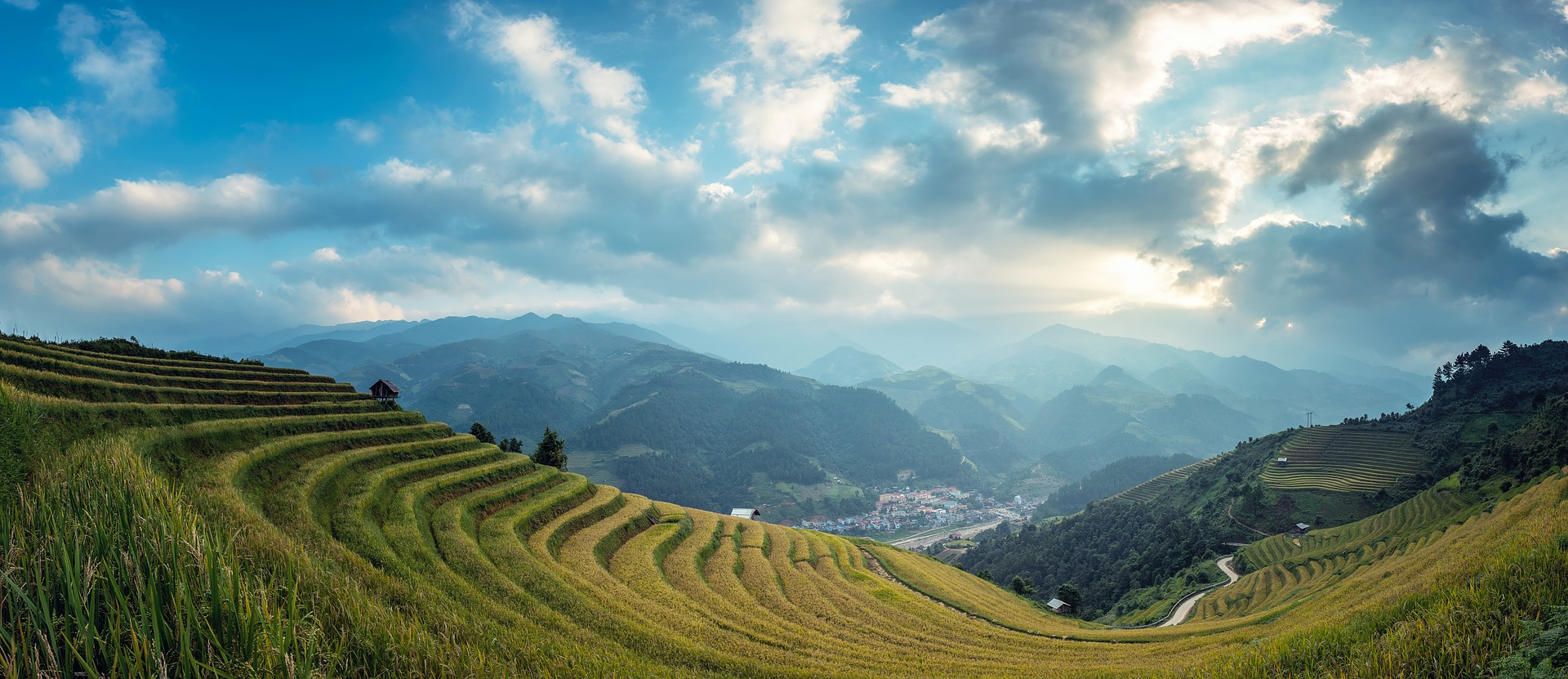 Rolling rice paddy fields on the side of hills facing a village in the valley with mountains beyond it. The sky is filled with clouds with the sun breaking through.