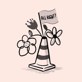 "A traffic cone with flowers sticking out the top and a flag saying ""All Right?"" on it. A tribute to the Christchurch earthquake on 22 February 2011"