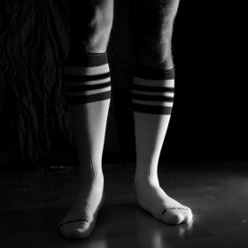 Knee-high athletic socks on a man's legs in black and white
