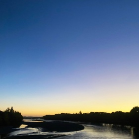 Waimakariri River flowing away from the Southern Alps, with the sun almost set on the horizon. The sky is dark blue at the top to yellow on the horizon.
